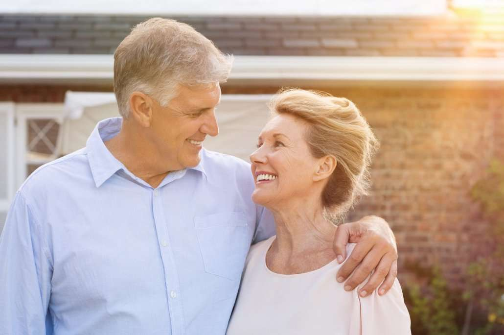 a senior couple smiling and looking at one another